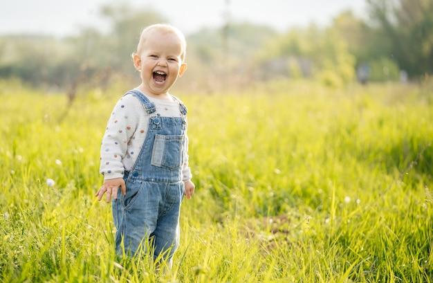 Caminhadas infantis de verão. a criança experimenta emoções de alegria na floresta em um prado em um dia ensolarado. Foto Premium