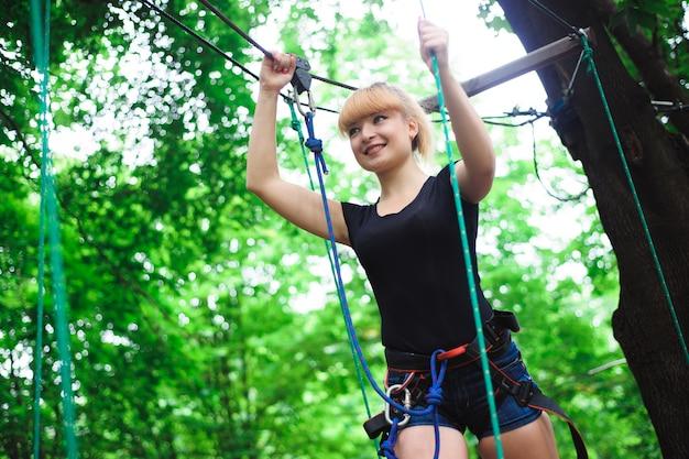 Caminhadas no parque corda jovem garota na faixa de seguro. Foto Premium