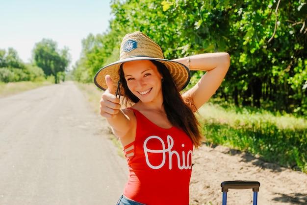 Caminhando a mulher em um chapéu de palha e em uma camisa vermelha que dão os polegares sorriso acima. Foto Premium