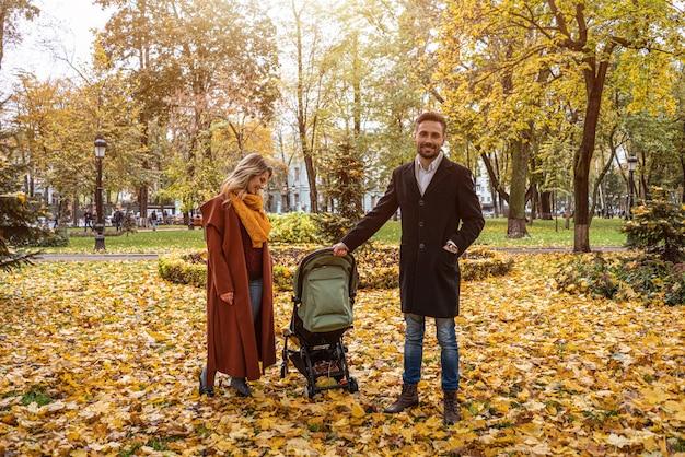 Caminhando em um parque de outono com uma jovem família com um bebê recém-nascido em um carrinho Foto Premium