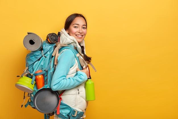 Caminhante asiática positiva fica de lado para a câmera, carrega uma mochila grande com coisas necessárias para a viagem, faz uma viagem de aventura emocionante, isolada sobre a parede amarela Foto gratuita