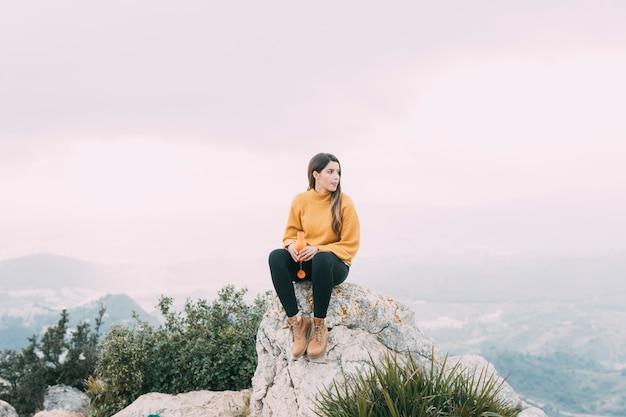 Caminhante sentado na pedra Foto gratuita