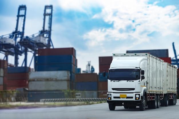 Caminhão branco do recipiente da carga na indústria de logistics.transportation do porto do navio no negócio portuário. Foto Premium