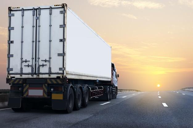 Caminhão branco na estrada rodovia com contêiner, transporte na via expressa de asfalto Foto Premium