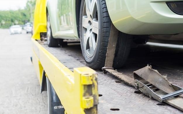 Caminhão de avaria do transportador de carro durante o trabalho usando o transporte de cinto bloqueado outro carro verde Foto gratuita