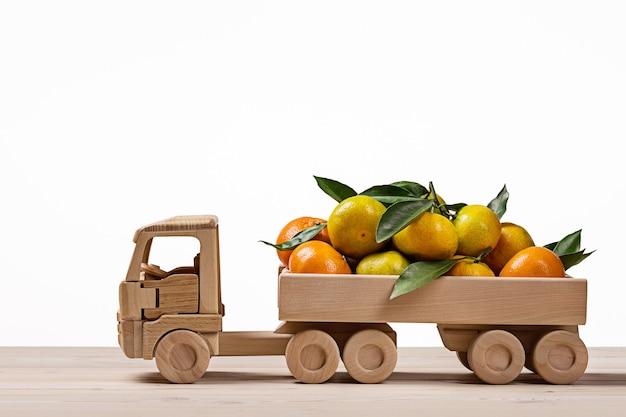 Caminhão de brinquedo com tangerinas e clementinas. Foto Premium
