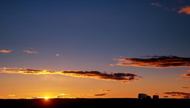 Caminhão de carros em uma estrada ao nascer do sol com sol lindo Foto Premium
