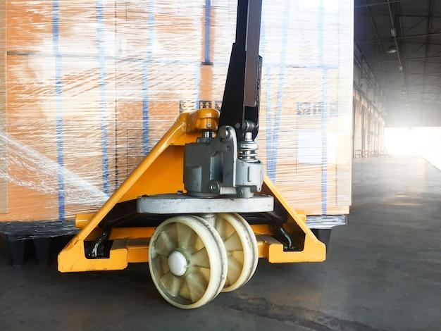 Caminhão de pálete da mão com a pálete da expedição para exportar. Foto Premium