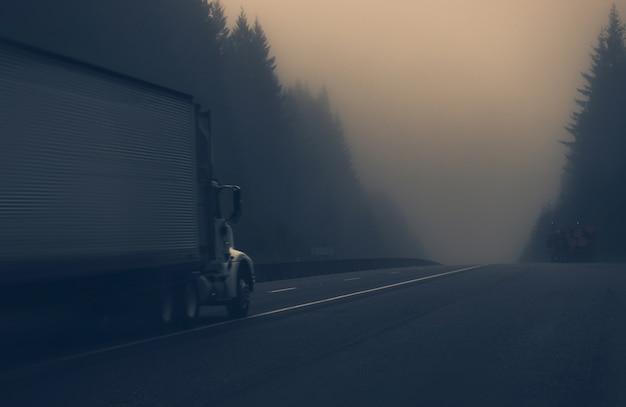 Caminhão na estrada nevoenta Foto gratuita