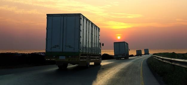 Caminhão na estrada rodovia com recipiente, logística industrial com céu do nascer do sol Foto Premium