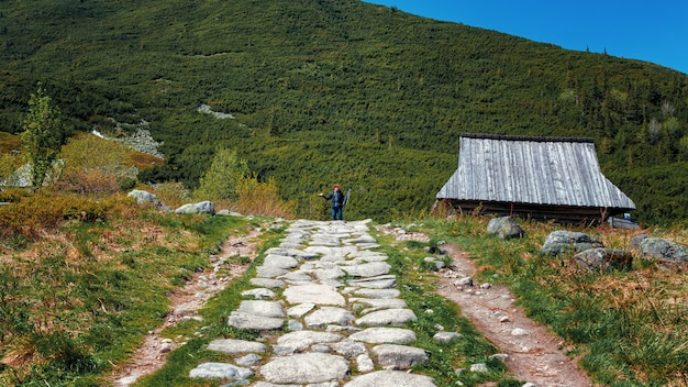 Caminho chapado branco no vale verde da montanha e fotógrafo longe Foto Premium