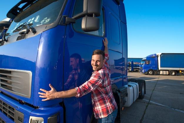 Caminhoneiro abraçando seu caminhão para transporte Foto gratuita