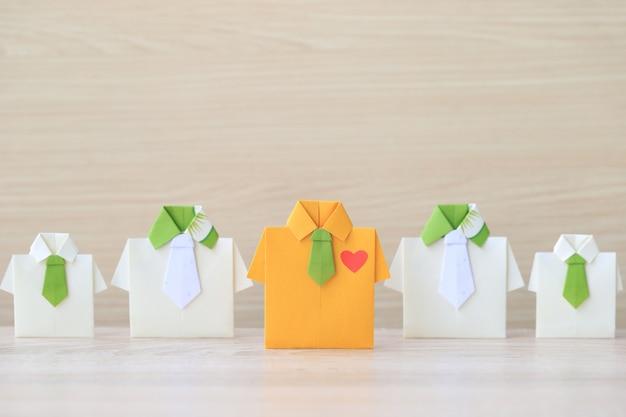 Camisa amarela de origami com gravata líder entre a pequena camisa amarela no fundo wooder Foto Premium