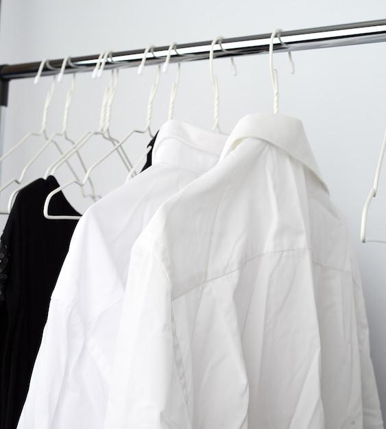 Camisas amassadas do homem branco penduradas em um cabide de metal Foto Premium