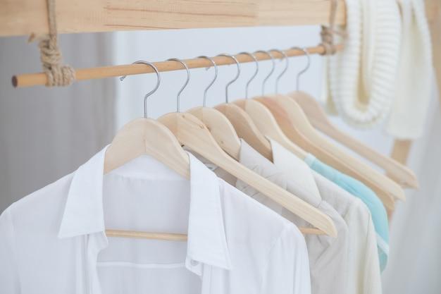 Camisas brancas penduradas em prateleiras de pano interno branco Foto Premium