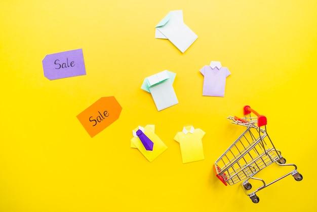 Camisas de papel de brinquedo brilhante perto de carrinho de compras e venda tags Foto gratuita