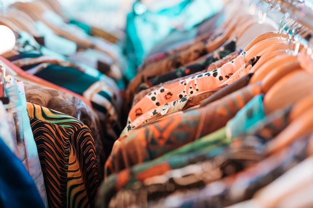 Camisas florais penduradas no cabide de madeira pendurado no trilho Foto gratuita
