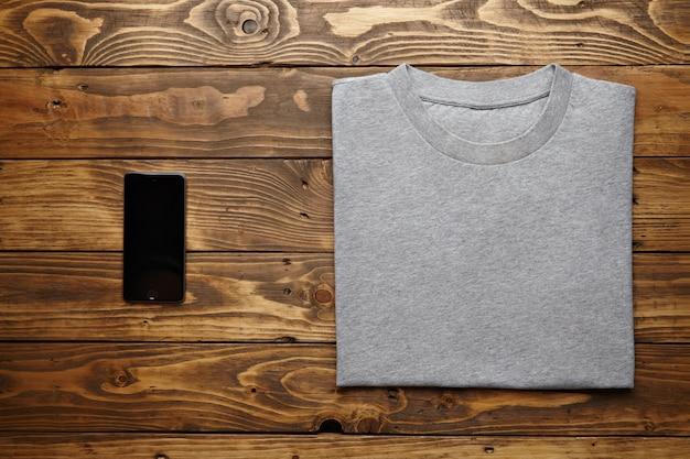 Camiseta cinza em branco dobrada com precisão perto do gadget de smartphone preto na vista de mesa de madeira rústica Foto gratuita