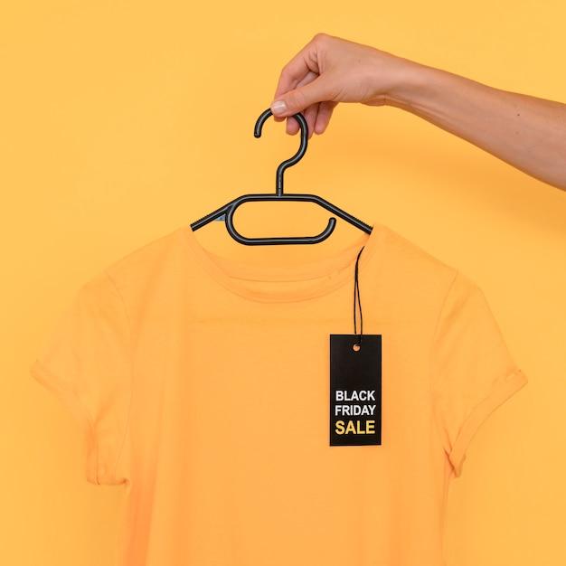 Camiseta preta em liquidação na sexta-feira no cabide Foto gratuita