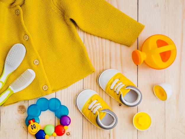 Camisola amarela vista superior com brinquedos Foto gratuita