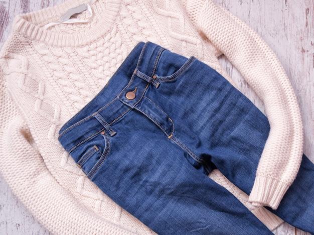 Camisola branca e calça jeans em um fundo de madeira, vista superior Foto Premium