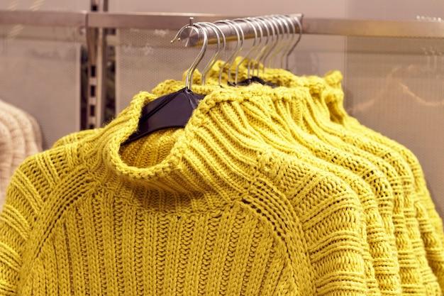 Camisolas amarelas penduradas em cabides na loja, conceito de compra de roupas Foto Premium