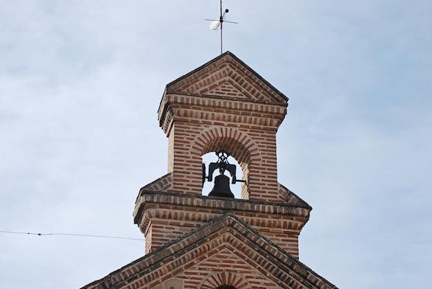 Campanário da capela com sino, cruz e vane Foto Premium