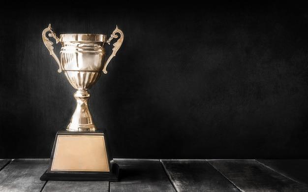 Campeão troféu de ouro na mesa de madeira com espaço de cópia de quadro-negro Foto Premium