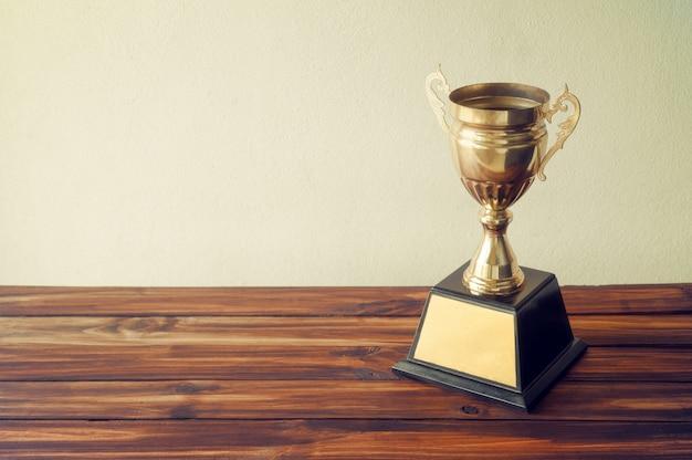 Campeão troféu de ouro na mesa de madeira com espaço de cópia pronto para seu projeto. Foto Premium