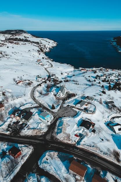Campo coberto de neve perto do corpo de água durante o dia Foto gratuita