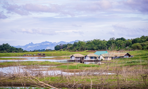 Campo perto do lago e montanha com céu nublado Foto Premium