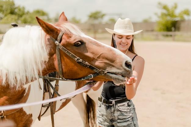 Camponesa alimentando um cavalo em uma fazenda Foto Premium