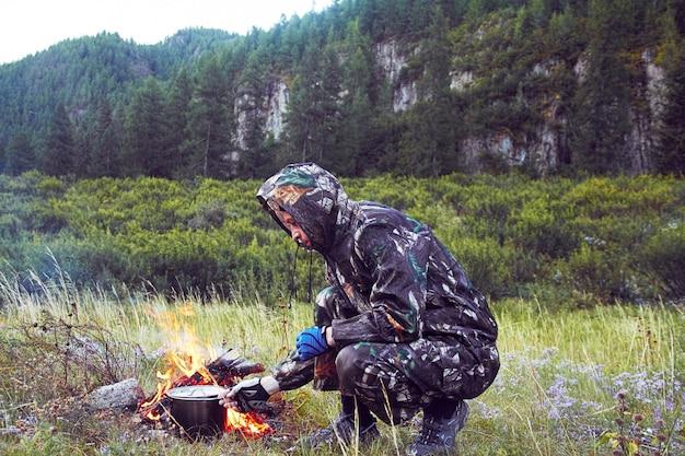 Camuflagem de homem preparando comida na fogueira sobreviver Foto Premium