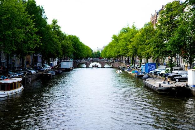 Canais de amesterdão, barcos a pé na água Foto gratuita
