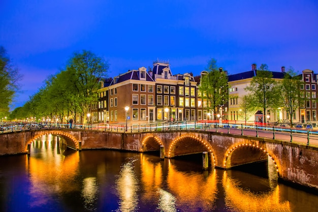Canal de amsterdão com as casas holandesas típicas durante a hora azul crepuscular na holanda, países baixos. Foto Premium