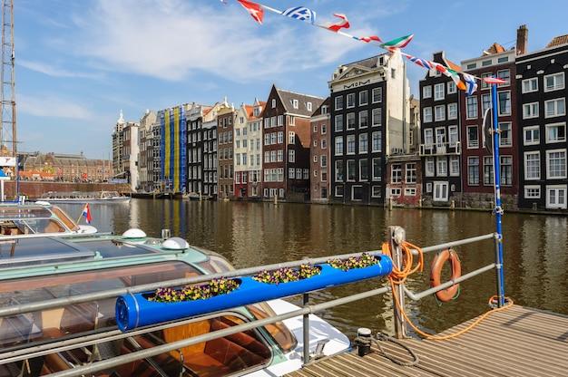 Canal houses of damrak, amsterdã, holanda Foto Premium