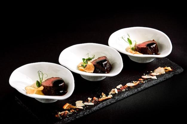 Canapés de atum com molho de vinho tinto e purê de aspargos com feijão Foto Premium