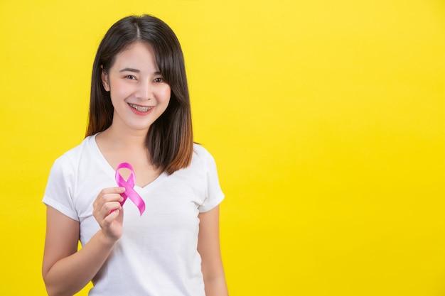 Câncer de mama, uma mulher em uma camiseta branca com uma fita de cetim rosa no peito, um símbolo para a conscientização do câncer de mama Foto gratuita