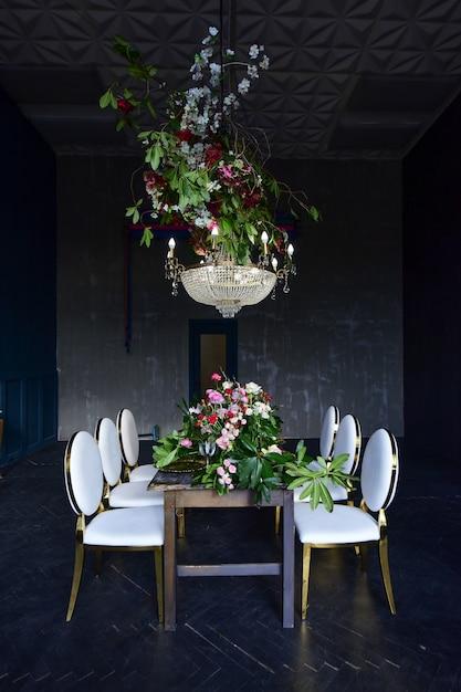 Candelabro de christal rico paira sobre a mesa de jantar com rosas vermelhas e vegetação Foto gratuita