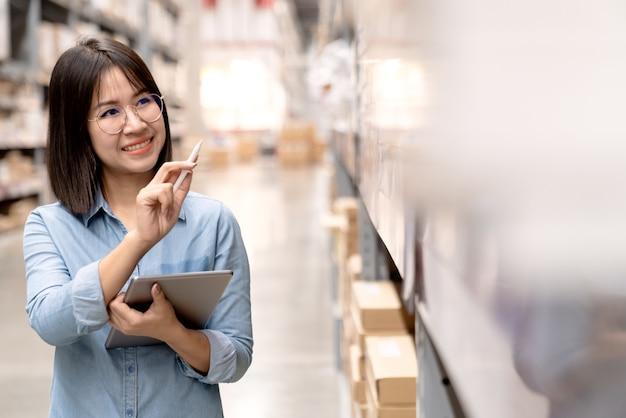Candid empregado asiático atraente ou pessoal trabalhando no estoque da loja Foto Premium