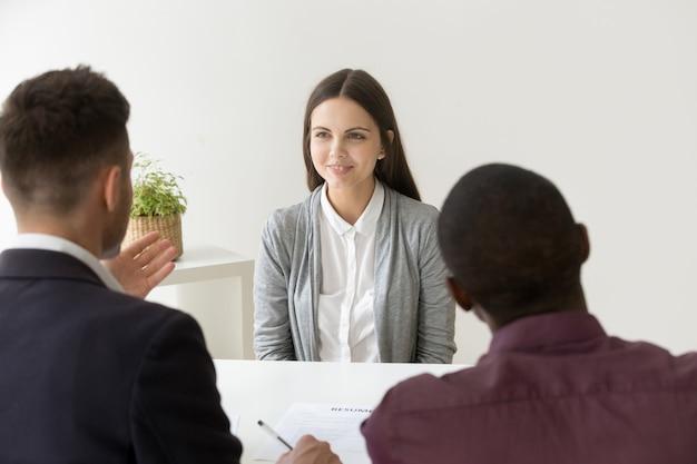 Candidato confiante sorrindo na entrevista de emprego com diversos gerentes de rh Foto gratuita