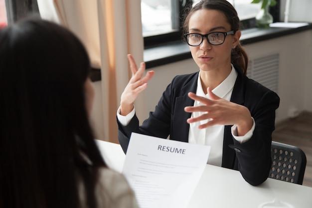 Candidato feminino milenar confiante em copos falando na entrevista de emprego Foto gratuita