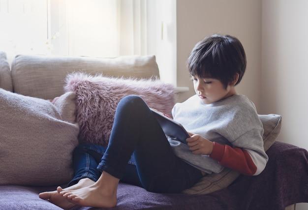 Cândido tiro menino bonitinho assistindo desenhos animados sobre tablet, retrato da escola garoto sentado no sofá com cara séria, jogando jogos no telefone inteligente. cena quente e aconchegante em tom pastel Foto Premium
