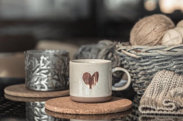 Caneca branca com coração e cesta de vime com bolas de linha Foto gratuita