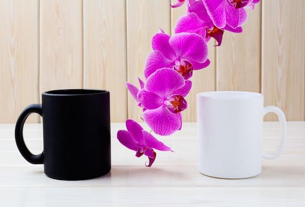 Caneca branca e preta com orquídea rosa Foto Premium