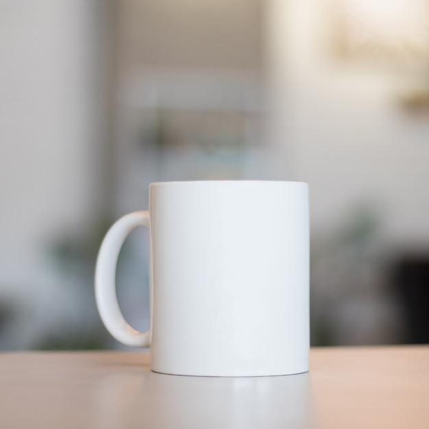 Caneca branca na tabela e no fundo moderno da sala. copo de bebida em branco para seu projeto. Foto Premium