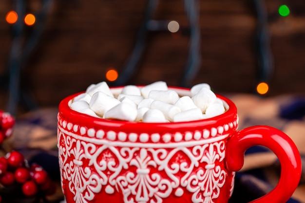 Caneca com cacau e marshmallows com fundo de luzes de guirlanda de natal aconchegante Foto Premium