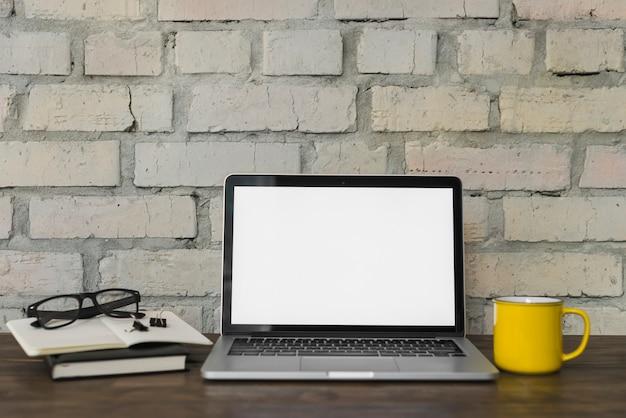 Caneca de café amarela; espetáculo; abra o laptop e artigos de papelaria na mesa de madeira com fundo de parede de tijolo Foto gratuita