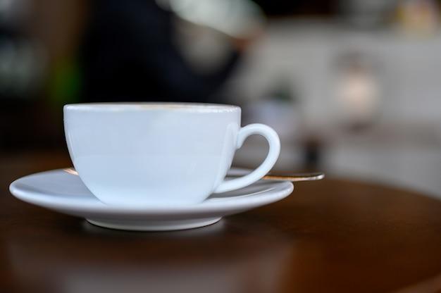 Caneca de café branca colocada na mesa Foto Premium