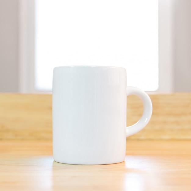 Caneca de café branco no fundo de madeira no ambiente da manhã. Foto Premium